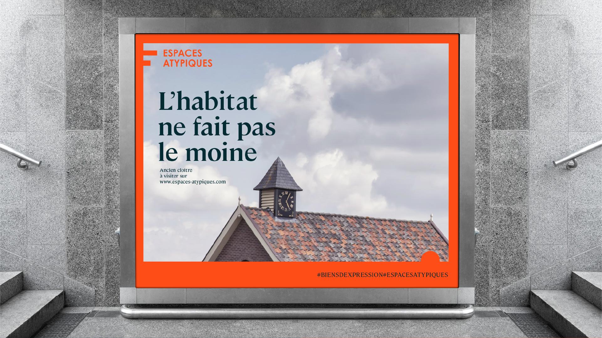 Application sur un grand panneau publicitaire de la nouvelle identité Espaces Atypiques, le texte dit : L'habitat ne fait pas le moine